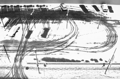 Another snowy morning in Denver gives me another excuse to pull out a snowy photo! I like the tire track patterns, and the obvious spots where people left early, trying to beat the downtown blizzard rush hour. I also noticed that the tracks at the exit, combines with the two arcs to right to form two letter P's, which makes me think of the Public Parking signs I see around. Not my best photo ever, but at least it's a bit different.   This was shot last spring. I took off a bit early from work and went for a long walk around downtown. After over an hour of getting pelted by big, wet snowflakes and chill winds I had just about had enough. I decided to head up to the roof of a parking garage, partially for a new perspective but mostly for a couple minutes in a heated elevator. The roof hadn't been plowed, so it had drifts up to my knees. After slogging my way to all four corners in search of views, I'd had enough. I went straight to the bar to get a few pints of warmth before heading home.
